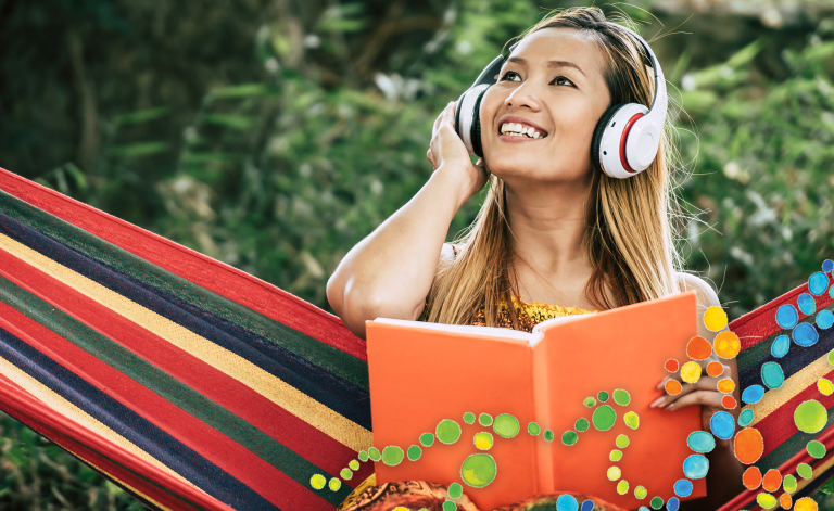 woman wearing headphones and reading a book