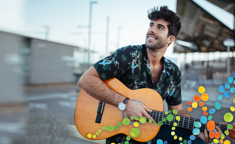 man smiling while playing the guitar